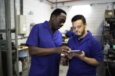 Two male work colleagues, one with Down syndrome, use a digital tablet at work in an industrial setting.