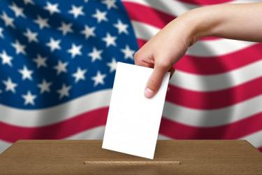 Photo of a hand dropping a ballot into a ballot box, with the American flag in the background