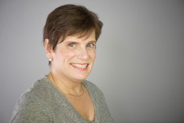 Professional headshot of Deb Cotter wearing a gray v-neck sweater with a gold necklace and pearl earrings