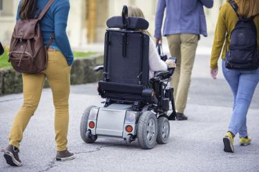 Photo shows students' backs as they walk on campus on a sidewalk. Two of the students are wearing backpacks and the student in the middle is using a power wheelchair.