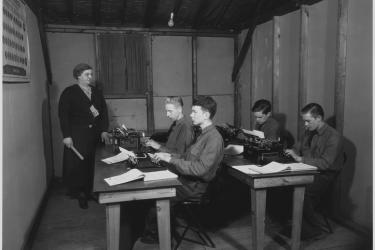 This vintage black and white photo displays a typing class with two rows of tables with two male students at each table with typewriters in front of them. A female instructor is at the front of the classroom with a ruler in her hand.