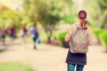 Back of female college student with brown hair and gray backpack walking away from the camera.