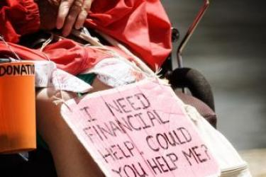 "A photo shows the chest down of a female disabled power wheelchair user in a red jacket with a sign that reads, ""I need financial help. Could you help me?"" written on a pink piece of cardboard and hanging by a string from her lap. There is an orange plastic cup that reads ""Donations"" hanging from the armrest of her wheelchair."