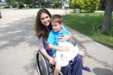 A mother and son, sit outside in a driveway facing forward. Both are smiling. The mother is a wheelchair user. Her son, wearing shorts and sandals, sits on her lap holding a bunny rabbit.