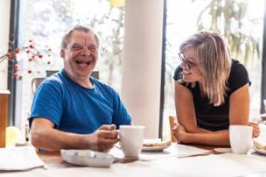 Older Caucasian man with Down syndrome, wearing a blue t-shirt, sits at a table with his right hand holding a white mug and a plate of food in front of him. He is laughing while a younger Caucasian woman with blonde hair and glasses and sitting to his left leans forward on the table and looks on, smiling.