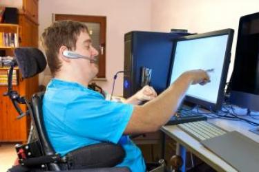 This image shows a man seated in an electric wheelchair from the side, facing a computer screen. His right hand, index finger extended, is touching t he computer monitor in front of him. His left hand is in a fist above the desk on which the computer monitor rests. He is smiling, wearing a headset with a microphone extending from the earpiece to the front of his mouth.