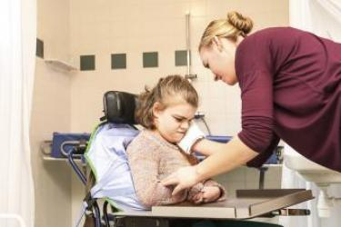 Young Caucasian girl with multiple disabilities wearing a pastel sweater is assisted by Caucasian nurse wearing burgundy medical scrubs.