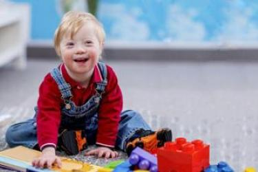 Smiling Caucasian toddler with Down syndrome playing on the floor with blocks and a book