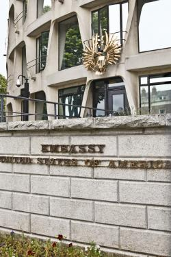 """Photo depicts concrete brick façade in front of gray windowed government building. The words """"Embassy United State of America"""" is imprinted in raised brass lettering on the concrete brick wall in front of the building."""