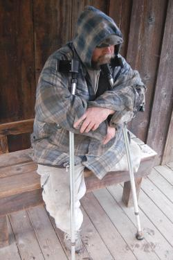 A bearded male amputee sits on a wood bench against a wood wall on a wood platform with his arms around Canadian crutches, which he has clutched to his chest. His chin rests on a crutch. He is wearing a camouflaged baseball cap that obstructs his eyes and a faded and torn blue plaid jacket with hoodie on, with the hood pulled over the hat. He wears pocketed gray sweatpants, which are also dirty and torn. He wears one gray athletic shoe, and his left pant leg is folded up under where his leg was amputated.
