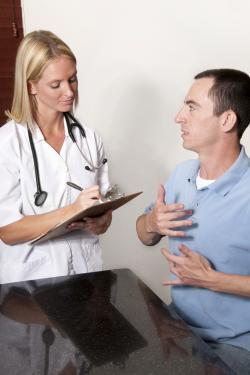 Caucasian man wearing a pale blue polo shirt uses sign language to communicate to a Caucasian female doctor with blonde hair and wearing a stethoscope around her neck and holding a clipboard as she listens and writes notes.