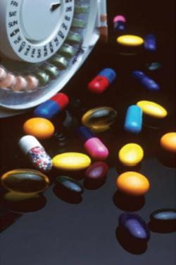 Photo of a variety of brightly colored prescription pills on a black glossy surface