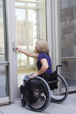 Caucasian woman in a wheelchair reaching forward to open a door