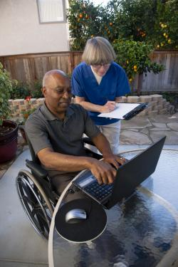 An African-American man wearing a gray polo shirt using a wheelchair types on a laptop as a Caucasian female healthcare worker writing on a clipboard and wearing a blue scrubs top looks on.